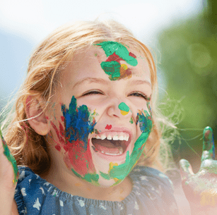A happy child playing with paint